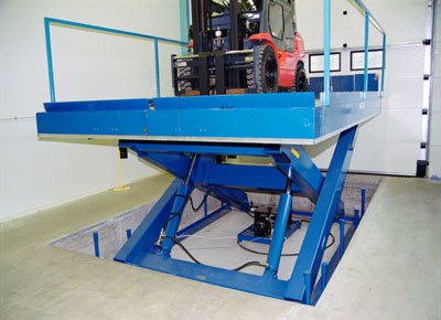 Loading and unloading lift table indoors in a pit, with folding handrails and roll-off guard.