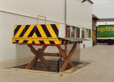 Loading and unloading lift table outdoors in a pit, with gates and metallic mesh.