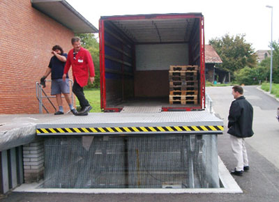 Loading dock lift table with mesh for vehicle access from dock or ground.