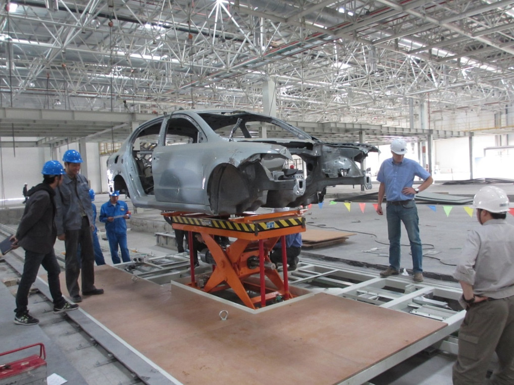 Spindle lift table for millimetre accuracy in handling automobile bodywork.
